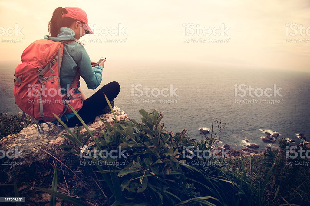 successful hiker use cellphone on seaside mountain peak rock stock photo