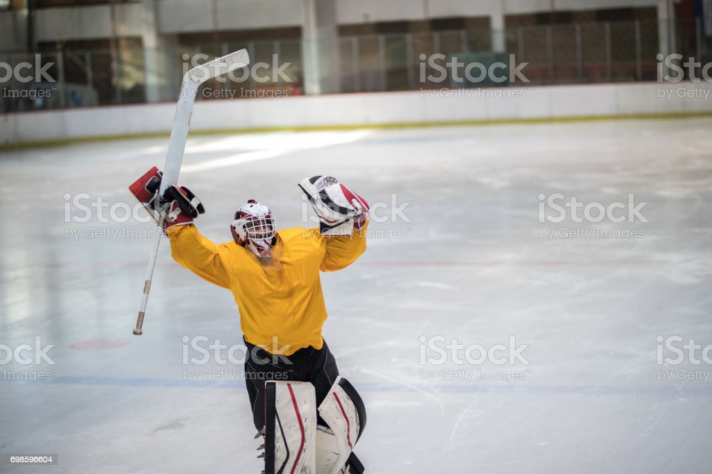 Successful ice hockey goaltender celebrating the victory with raised arms. stock photo