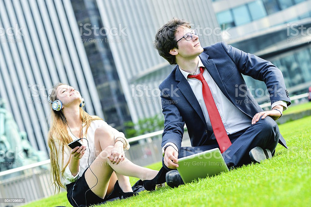 Successful Junior executives dynamics laying down on green grass royalty-free stock photo