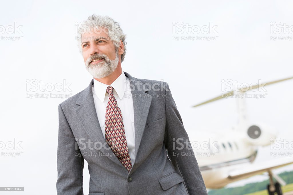 Successful looking businessman walking away from corporate jet royalty-free stock photo