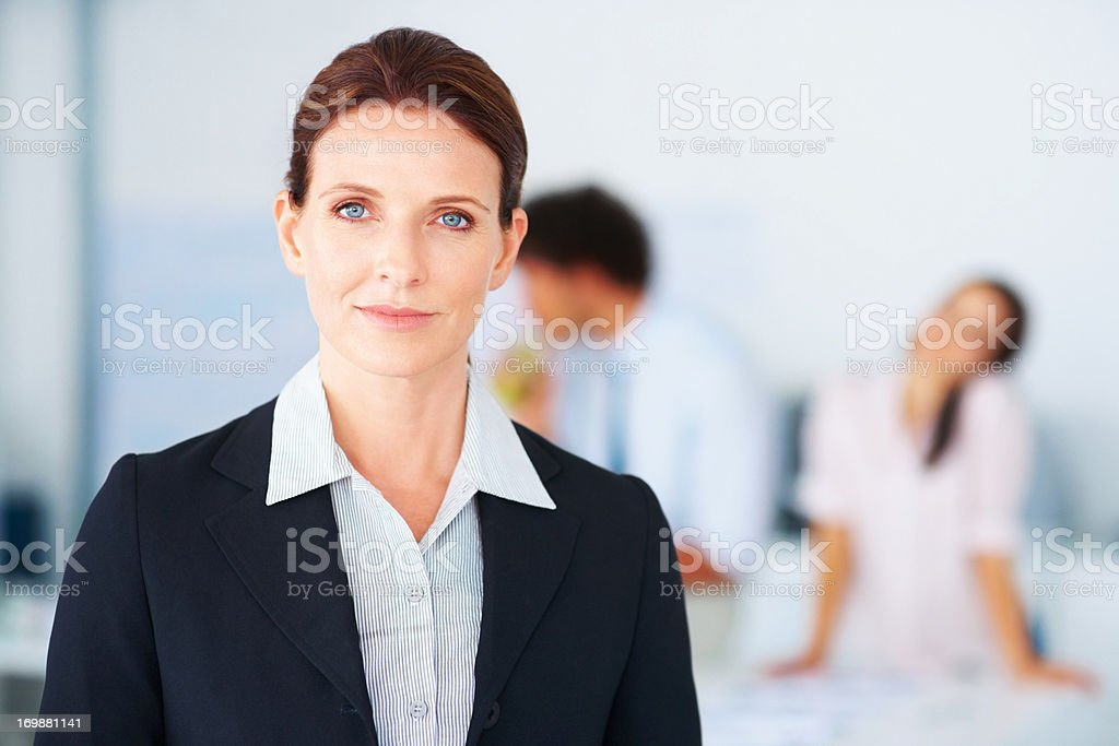 Successful magazine editor at work,colleagues at the back stock photo