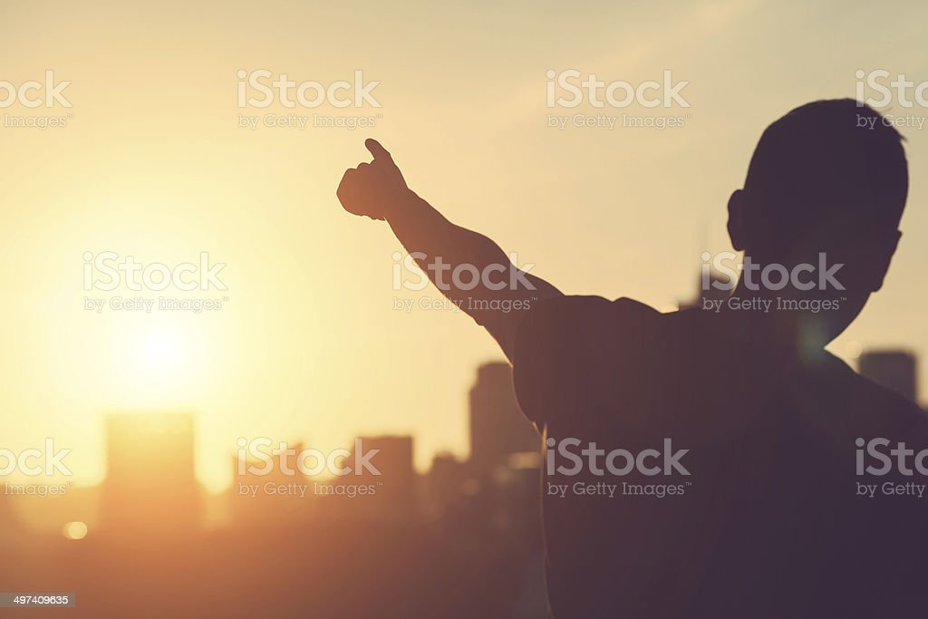 Successful Man aiming at Sunset stock photo