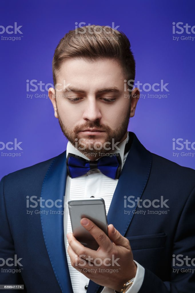 successful man in tuxedo and bow tie talking on phone stock photo