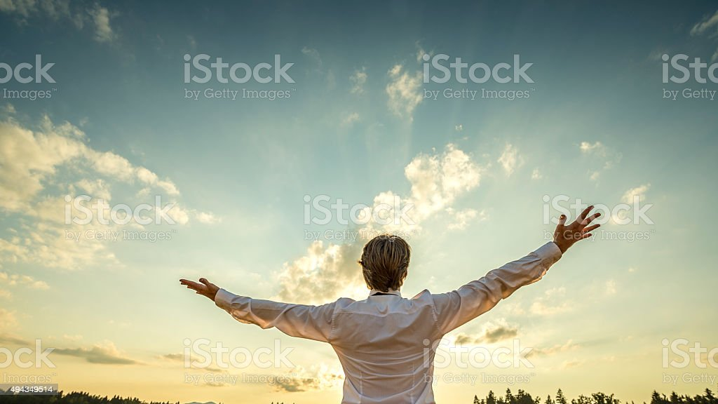 Successful man  standing  with his arms spread towards majestic sky stock photo