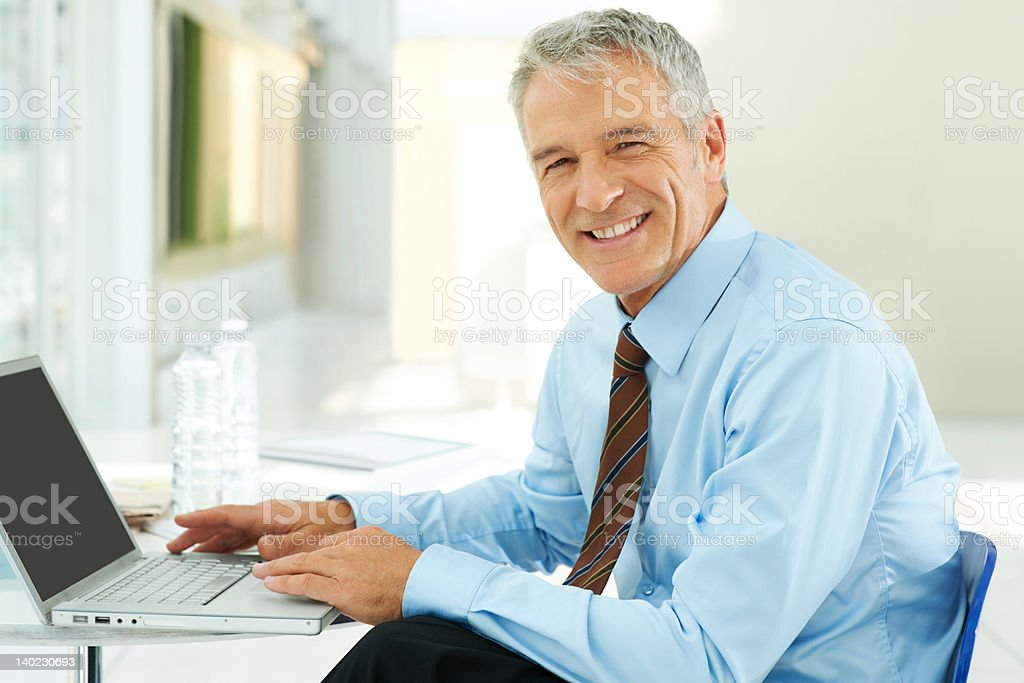 Successful mature businessman at his office desk stock photo