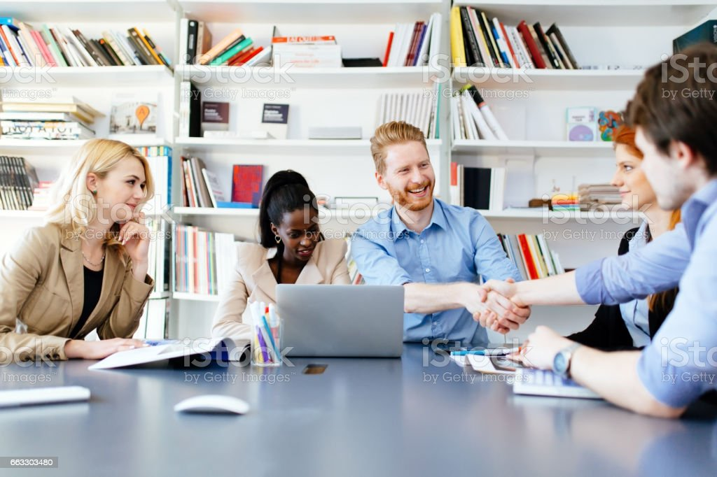 Successful partnership in business displayed by shaking hands in office stock photo