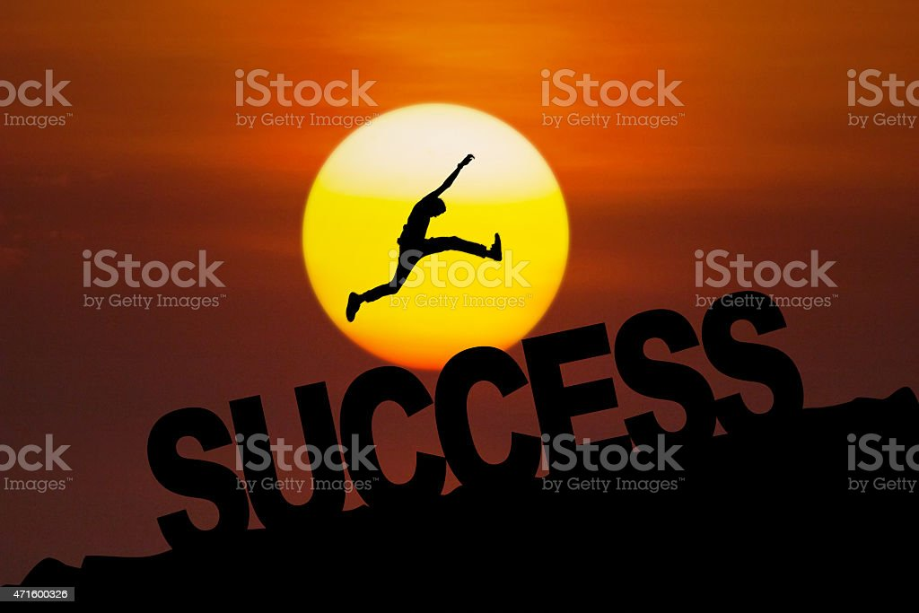 Successful person jumping at sunset stock photo