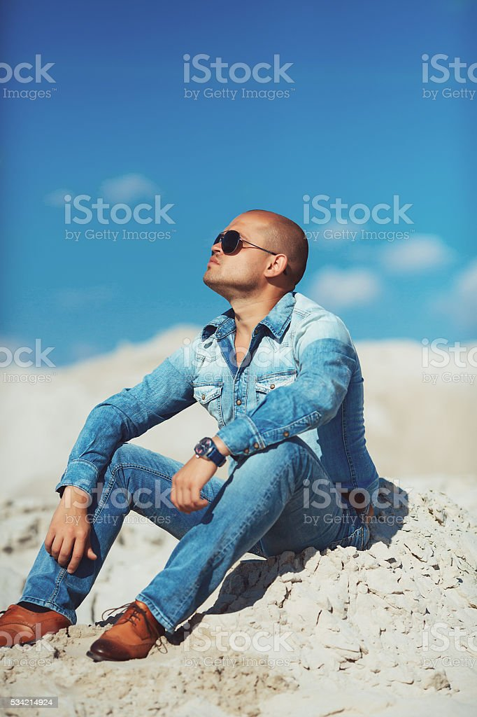 successful person sitting on the sand at sunset royalty-free stock photo