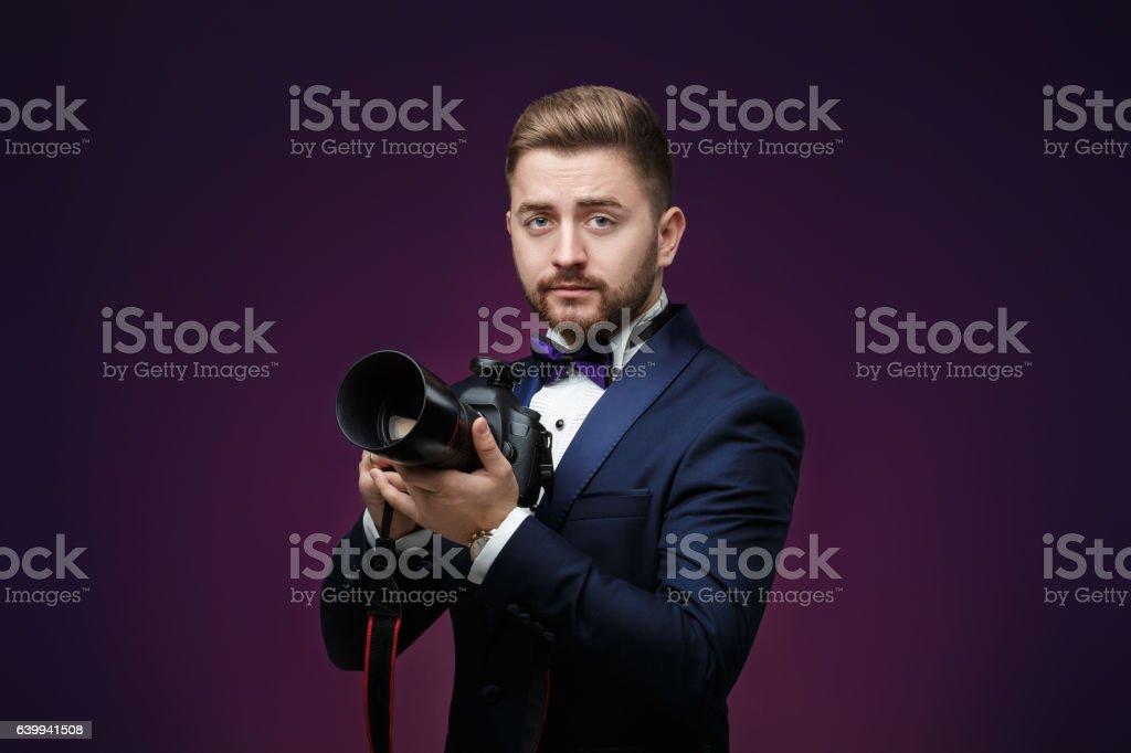 successful professional photographer in tuxedo use DSLR digital camera on stock photo
