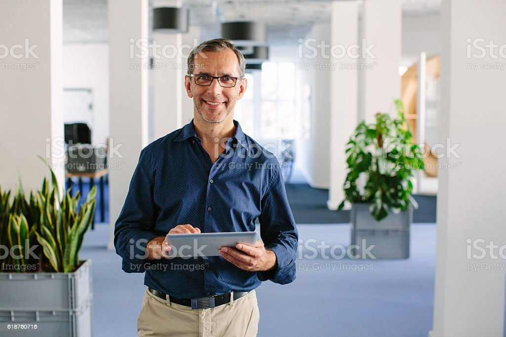 Successful senior businessman standing in office stock photo