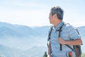 Successful senior man mountain hiker