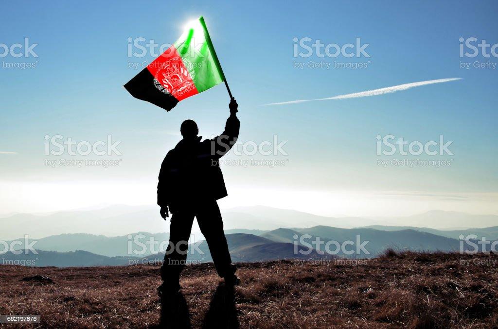 Successful silhouette man winner waving Afganistan flag on top of the mountain peak stock photo
