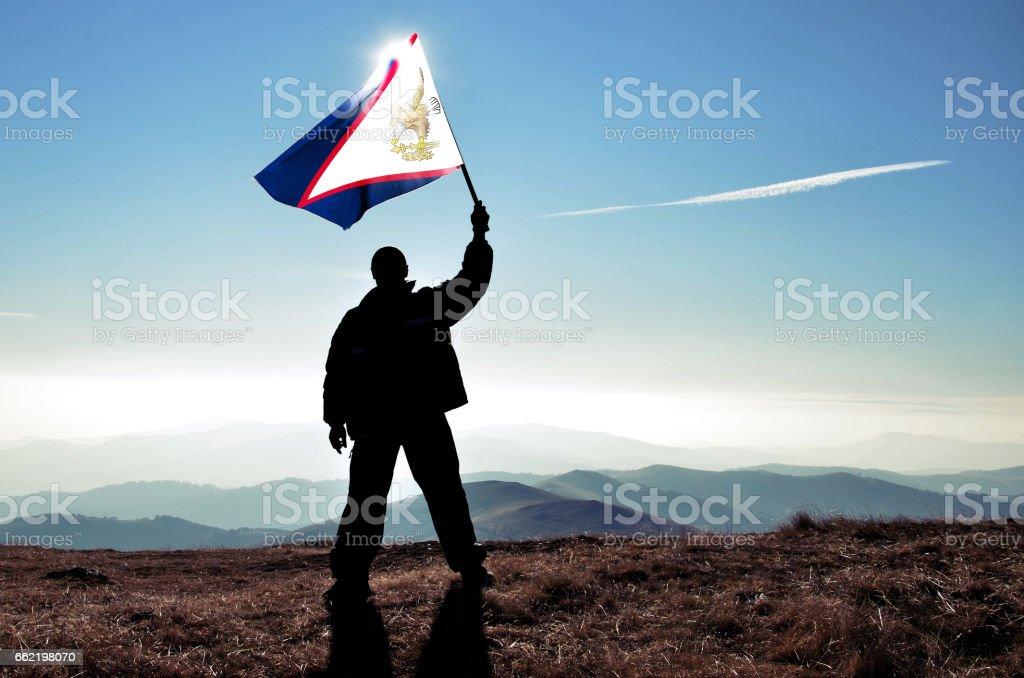 Successful silhouette man winner waving American Samoaman flag on top of the mountain peak stock photo
