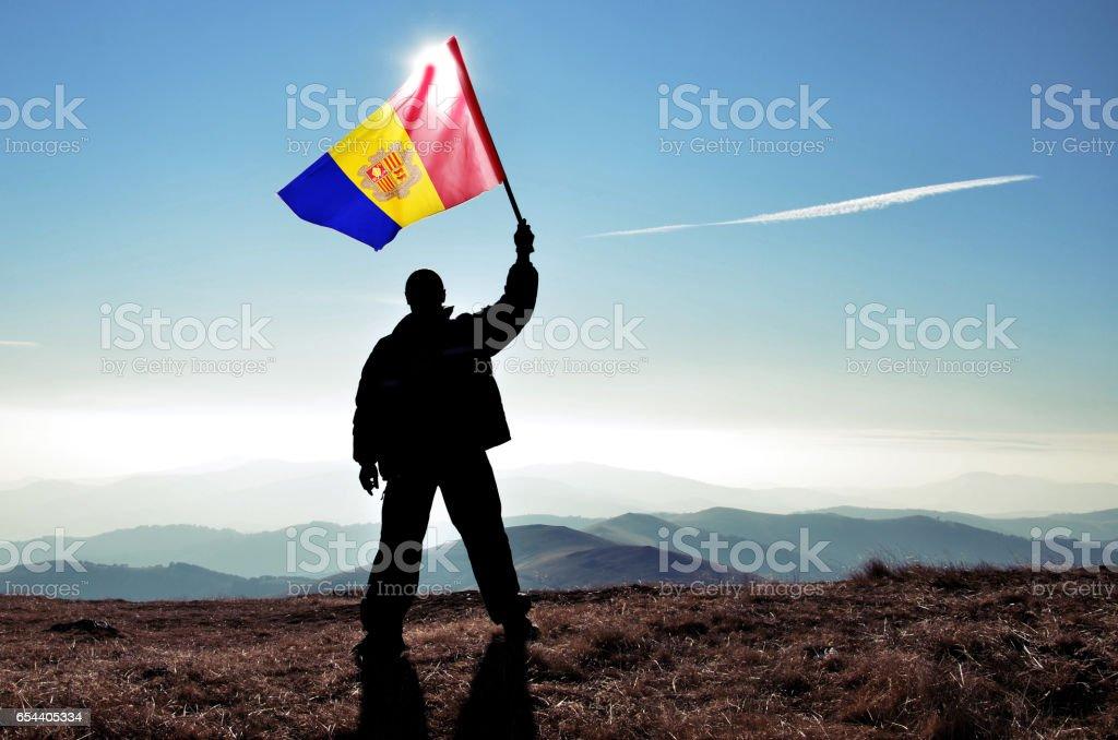 Successful silhouette man winner waving Andorra flag on top of the mountain peak stock photo