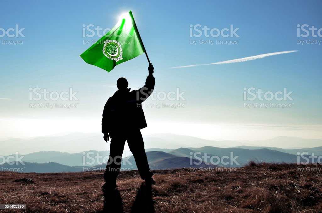 Successful silhouette man winner waving Arab League flag on top of the mountain peak stock photo