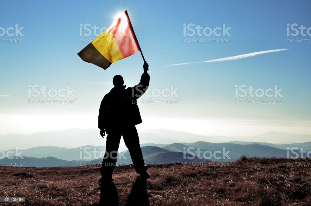 Successful silhouette man winner waving Belgian flag on top of the mountain peak stock photo