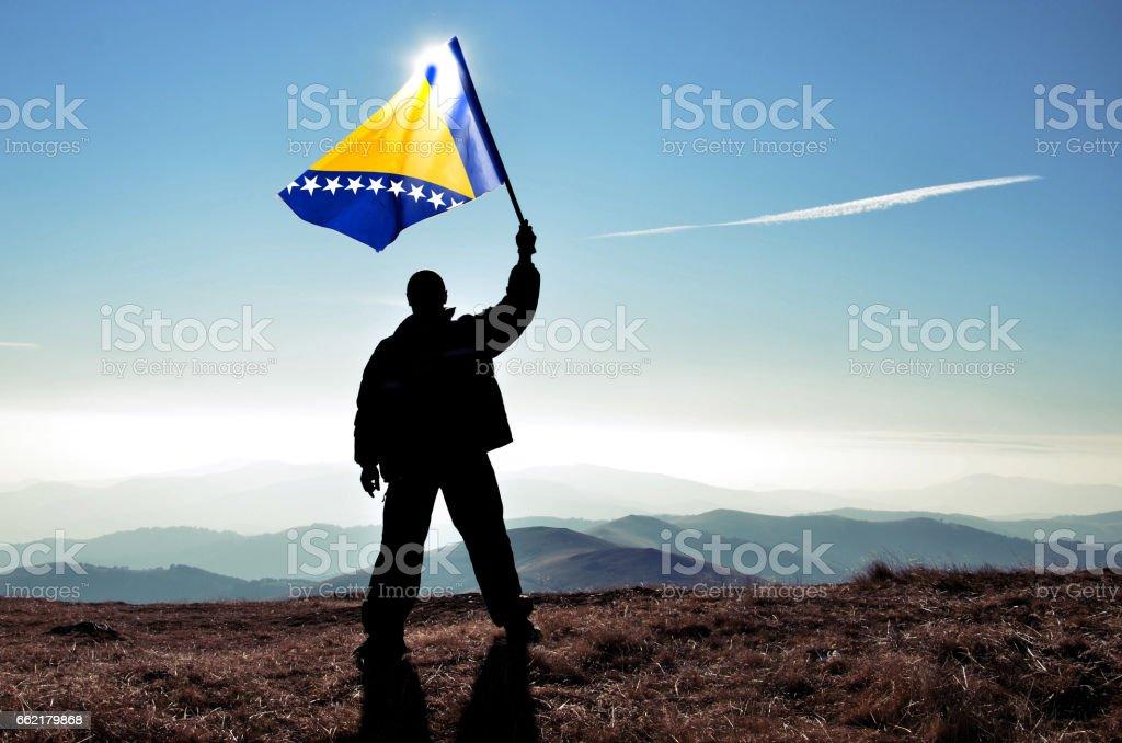 Successful silhouette man winner waving Bosnia And Herzegovinaflag on top of the mountain peak stock photo