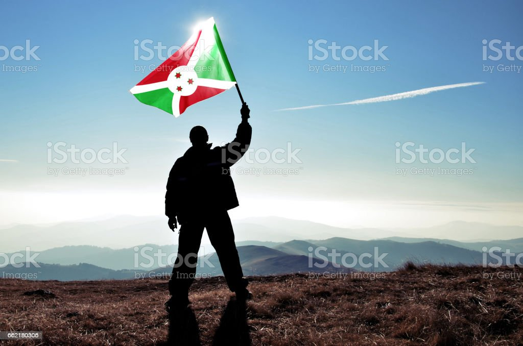 Successful silhouette man winner waving Burundi flag on top of the mountain peak stock photo