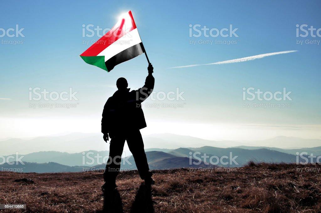 Successful silhouette man winner waving Sudan flag on top of the mountain peak stock photo