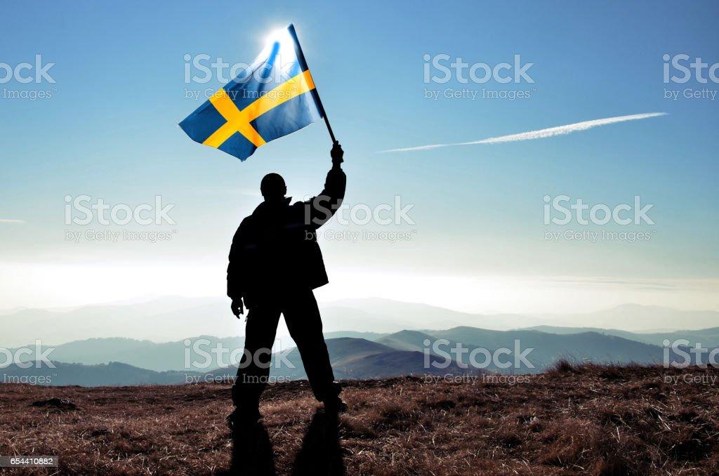 Successful silhouette man winner waving Sweden flag on top of the mountain peak stock photo