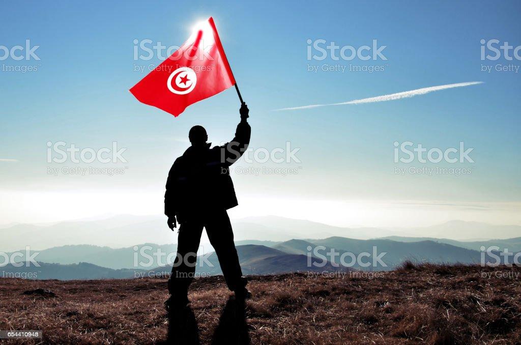 Successful silhouette man winner waving Tunisia flag on top of the mountain peak stock photo