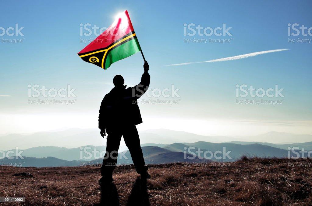 Successful silhouette man winner waving Vanuatu flag on top of the mountain peak stock photo