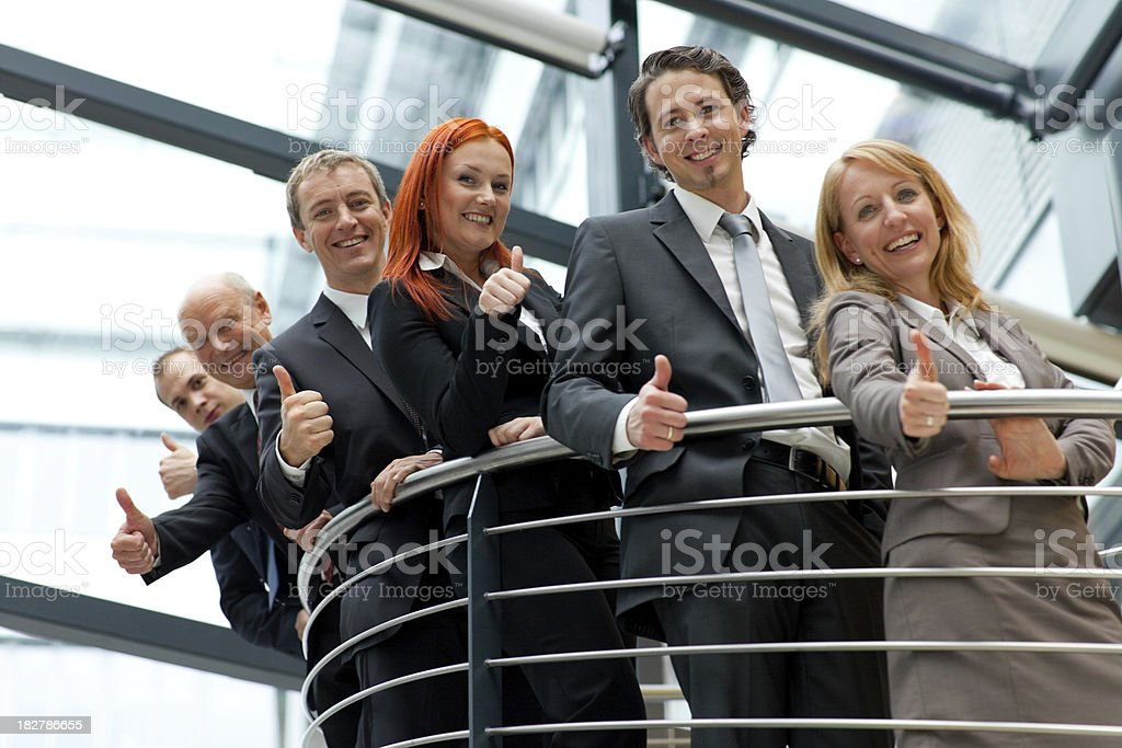 successful smiling business team showing thumbs up royalty-free stock photo