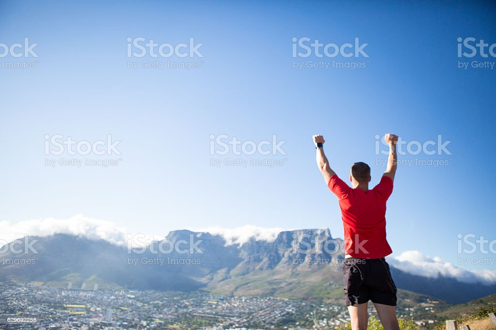 Successful sportsman stands on top of the mountain stock photo