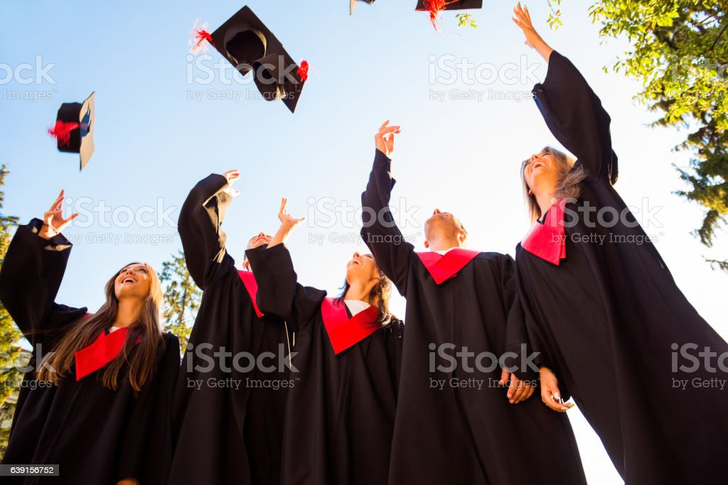 Successful students with congratulations together throwing up graduation hats stock photo