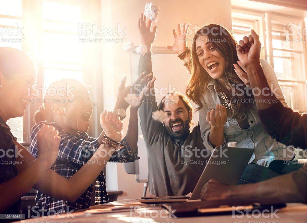 Successful team celebrating their business achievement in the office. stock photo
