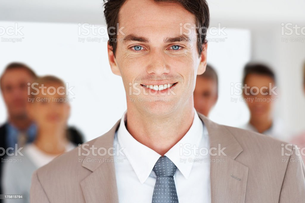 Successful team leader with colleagues in background stock photo