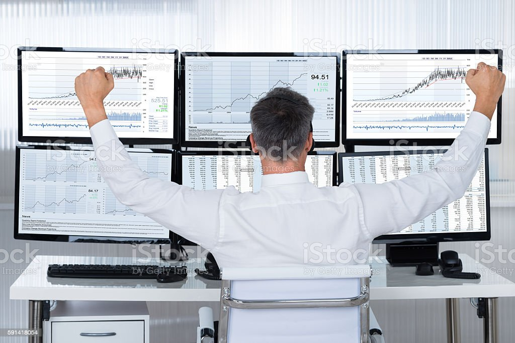 Successful Trader With Arms Raised Looking At Graphs On Screens stock photo