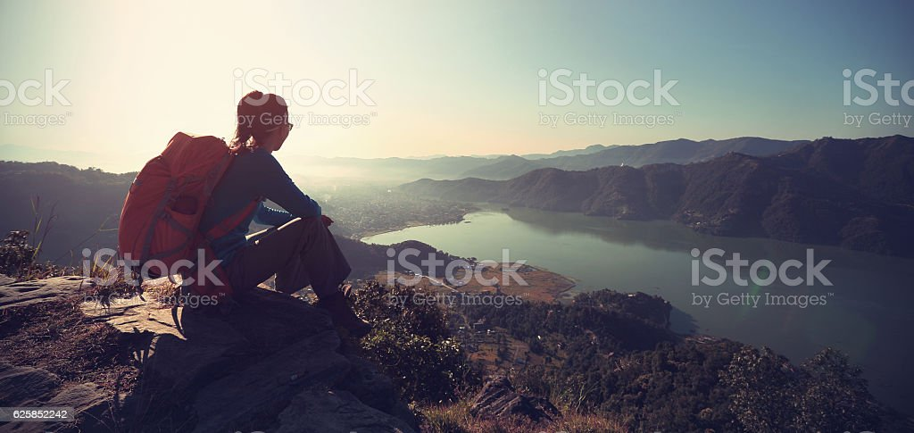 successful woman backpacker enjoy the view at mountain peak stock photo