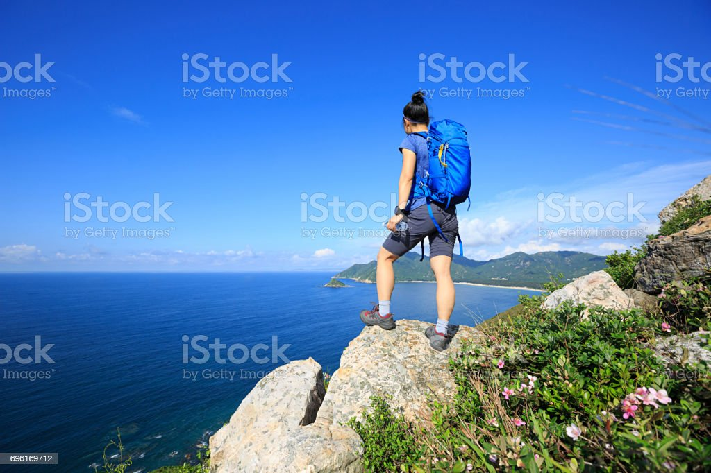 successful woman backpacker enjoy the view on seaside mountain rock stock photo