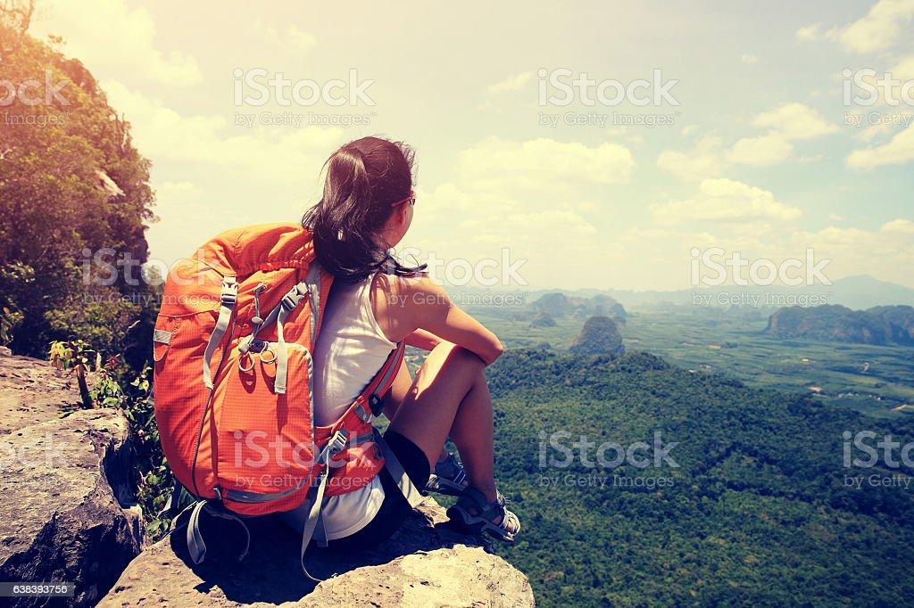 successful woman backpacker hiking on mountain peak cliff stock photo