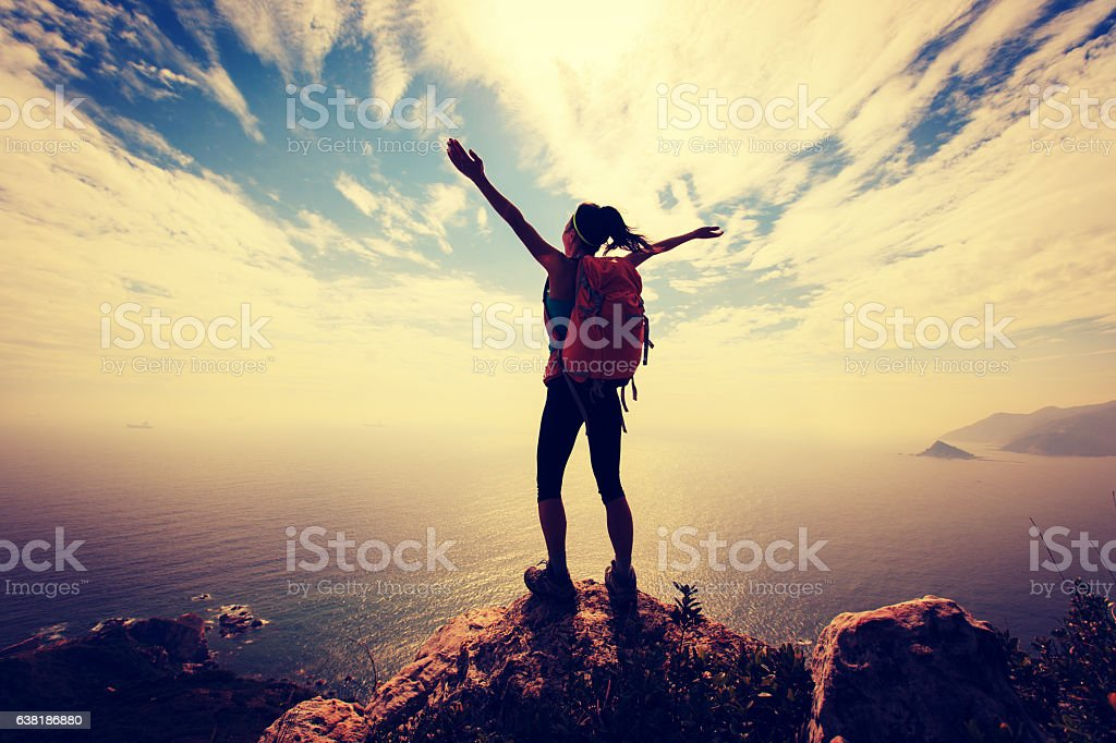 successful woman backpacker hiking on mountain peak stock photo