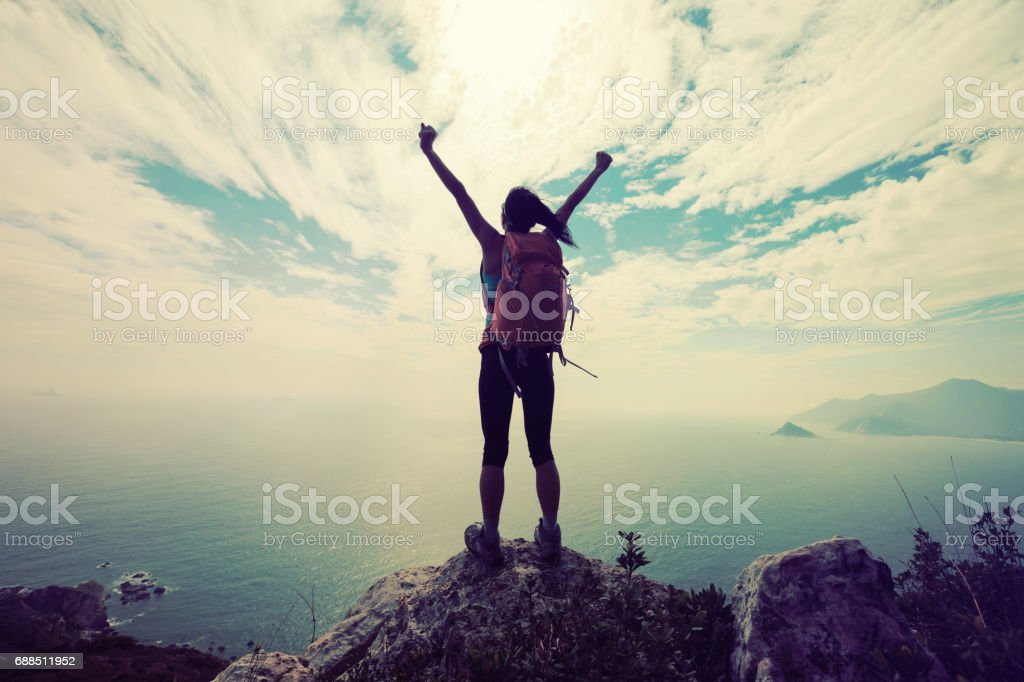 successful woman backpacker hiking on mountain peak stock photo