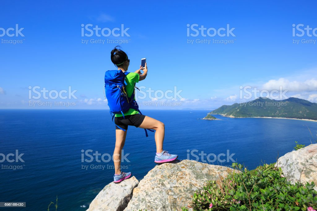 successful woman backpacker use smartphone on seaside mountain rock stock photo