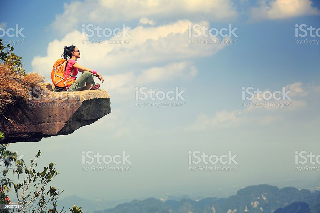 successful woman hiker enjoy the view on mountain top cliff stock photo