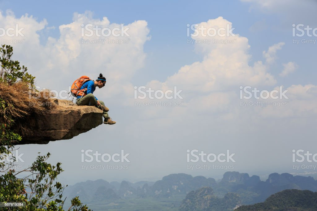successful woman hiker enjoy the view on mountain top rock stock photo