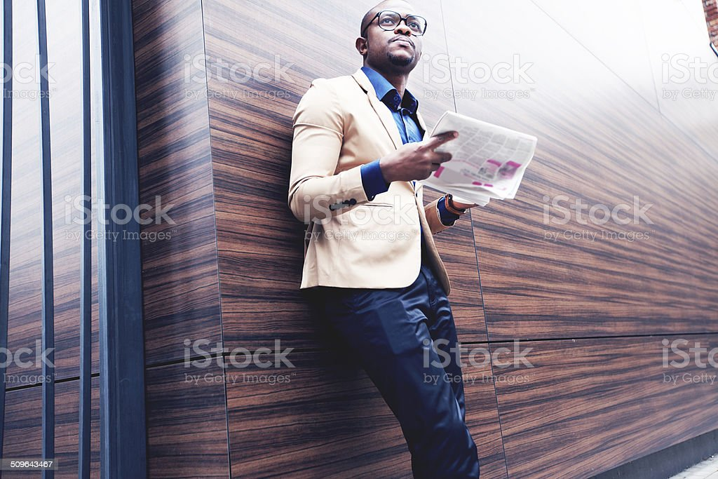 Successful young african man reading a newspaper stock photo
