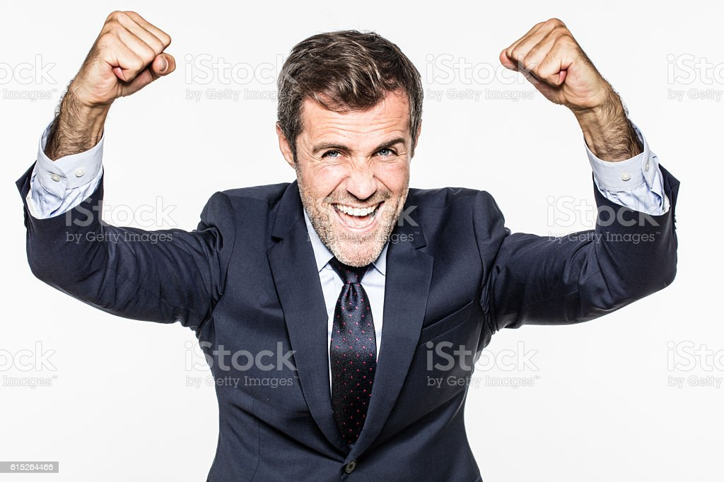 successful young bearded businessman with victorious arms raised smiling stock photo