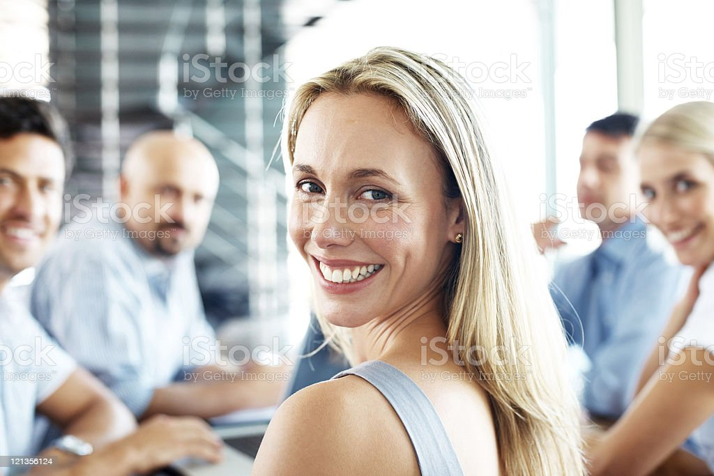 Successful young businesswoman looking over her shoulder stock photo