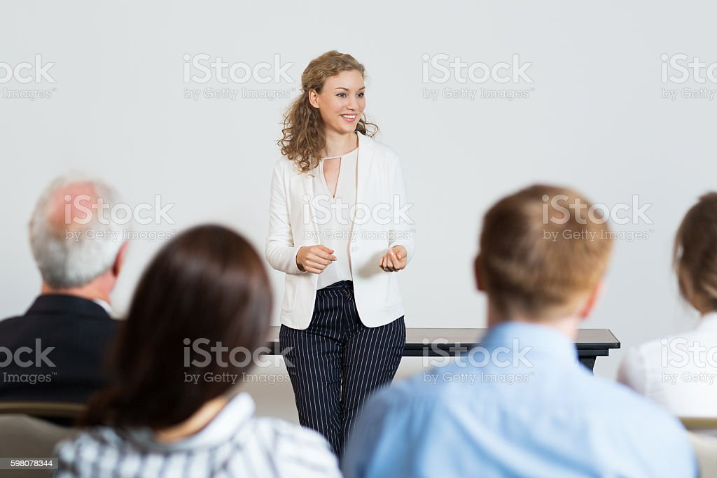 Successful Young Businesswoman Speaking in front of Audience at stock photo