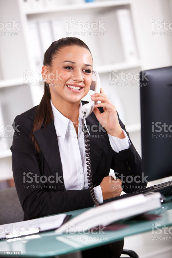 Successful young businesswoman using computer and talking on phone royalty-free stock photo