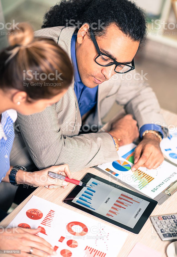 Successful young entrepreneurs analyzing stock market data in office stock photo