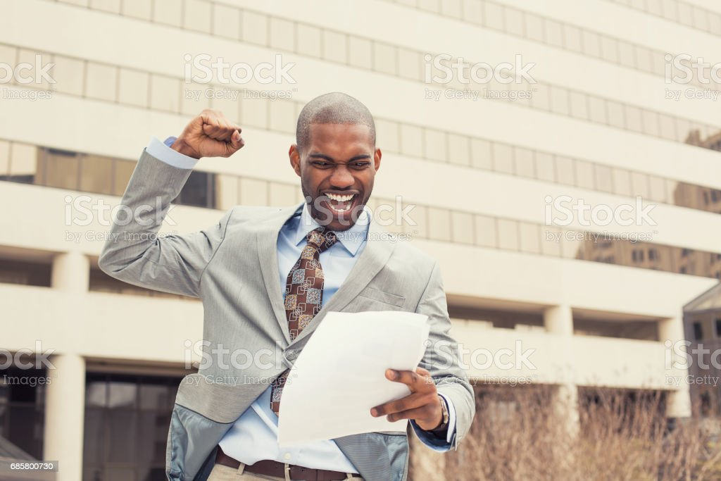 Successful young professional man celebrates success holding new contract documents stock photo