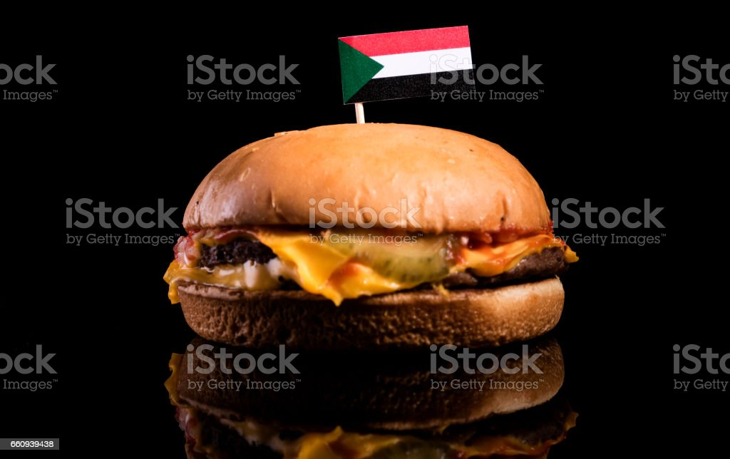 Sudanese flag on top of hamburger isolated on black background stock photo