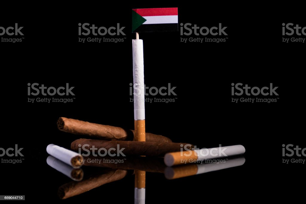 Sudanese flag with cigarettes and cigars. Tobacco Industry concept. stock photo