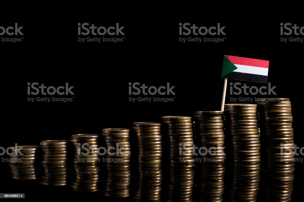Sudanese flag with lot of coins isolated on black background stock photo
